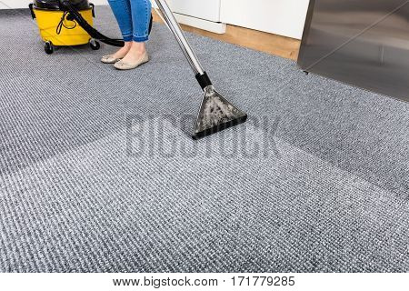 Close-up Of A Cleaning Carpet With Vacuum Cleaner