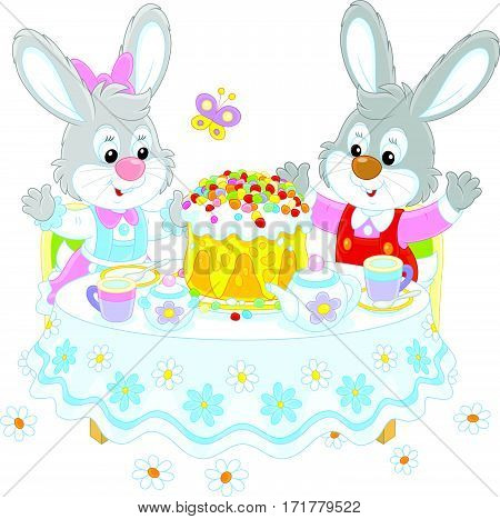 Easter rabbits at the tea table with a decorated holiday cake