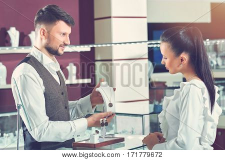Helpful jeweler. Handsome young male jeweler selling a necklace at his store woman choosing jewelry at the shop client customer consumerism shopper buyer people sale discount lifestyle concept