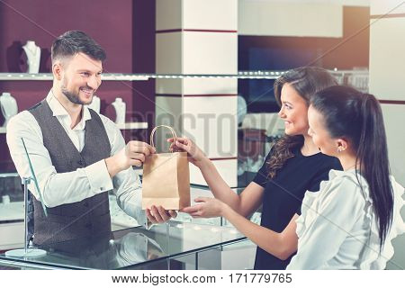 Girls buying jewelry. Cheerful female friends buying jewelry together from a professional jeweler receiving their purchased items in a shopping bag taking holding passing sale friends shopping concept