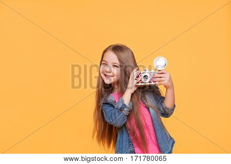 Young little girl photographer smiling and holding a retro camera isolated over bright yellow background