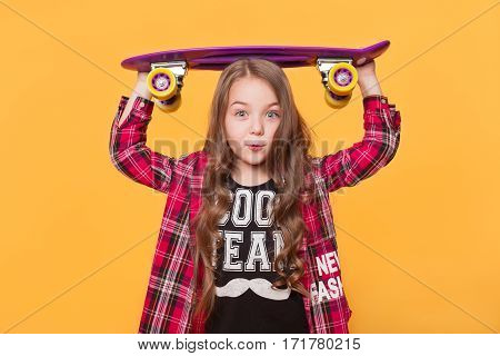 Kid's fashion. Portrait of a cute 6 year old girl wearing hipster casual clothes posing with skateboard on head over bright yellow background.