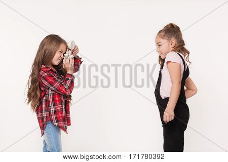 Two little girls taking a picture of each other isolated on white. Little kids sisters photographing one another