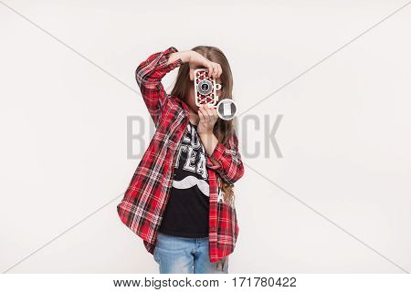 Beautiful little girl holding a instant camera. Fashion kid taking pictures with retro camera isolated on white background