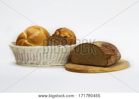 Bread slices and bread rolls are found in a white basket.