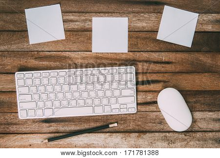 Creative vintage workspace table with paper notes key board pencil and mouse top view with Copy Space on vintage background.