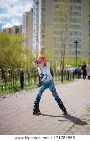 A toddler boy roller skating in sunny park. Child wearing protection elbow and knee pads wrist guards for safe roller skating ride. Active outdoor sport for kids.