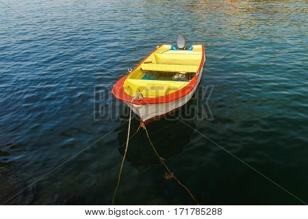 Old yellow with red fishing boat on the background of a calm sea water. Motor boat at the pier. Rowboat on the water.