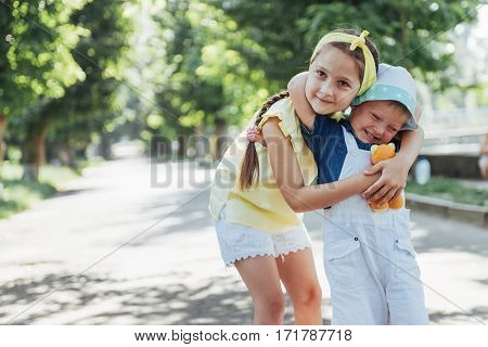 portrait of a little girl and her brother. Children playing outdoors on a sunny summer day. Family holidays.