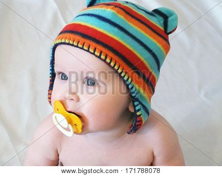 Baby boy with pacifier. Baby boy in knitted cap