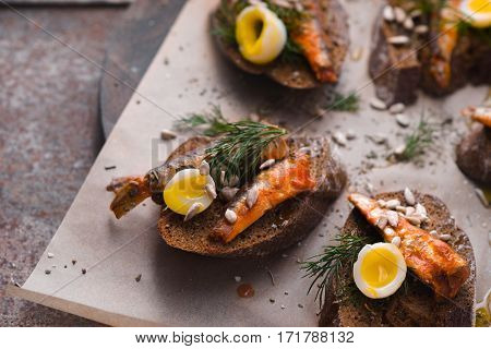 Sandwiches with sardines and quail eggs on a parchment horizontal