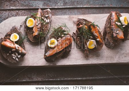 Sardines quail egg on rye bread on the stand horizontal