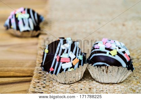 cake pop with coloured sprinkles on wooden table