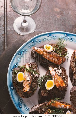 Sardines quail egg on rye bread and the glass vertical
