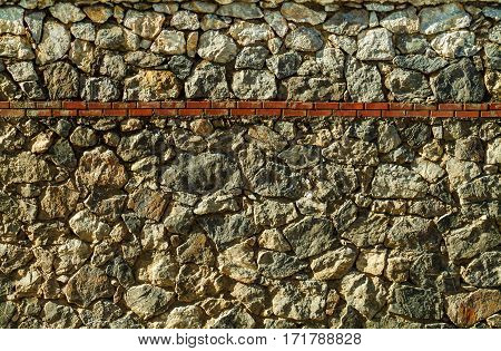 Wall Surface With Uneven Cracked Real Stones And Red Bricks