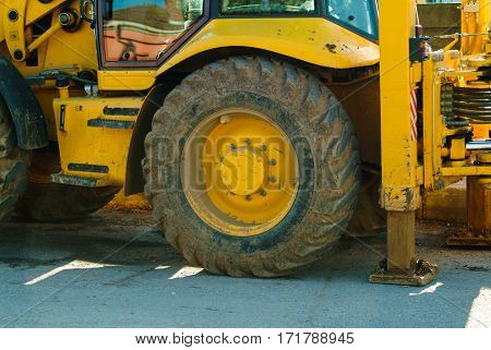 Close-up view of a dirty wheel of yellow heavy earth mover loader excavator construction machinery equipment