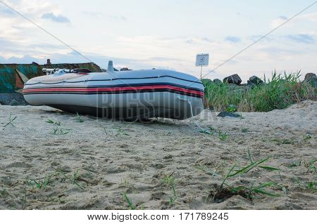 inflatable rubber boat lays on the sandy sea beach