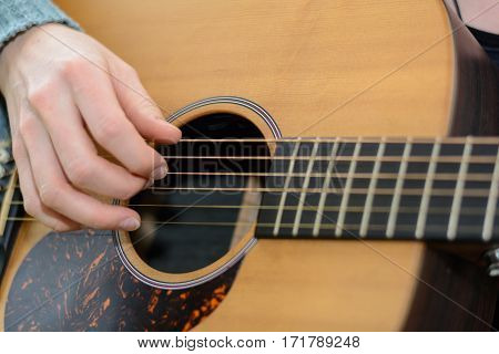 Person plucks song at old Western guitar - close-up