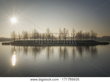 Rustic winter landscape with upcoming sun beautiful reflection of the trees