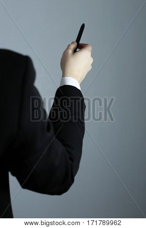 Business hand pointing on a gray background. A pen