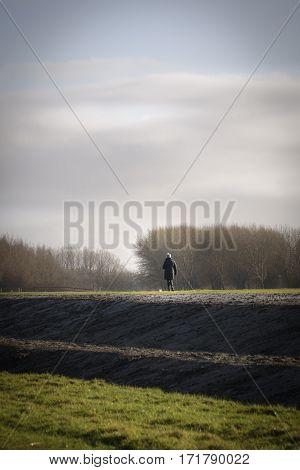 Woman walking on a dam in a typical Netherlands like landscape