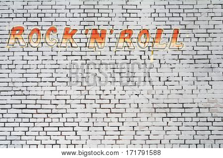 White brick wall with the inscription rock'n'roll for texture background.