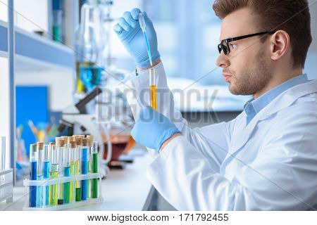 Side view of chemist making experiment in laboratory