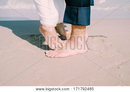 Close Up Male And Female Feet On White Sand, Kissing