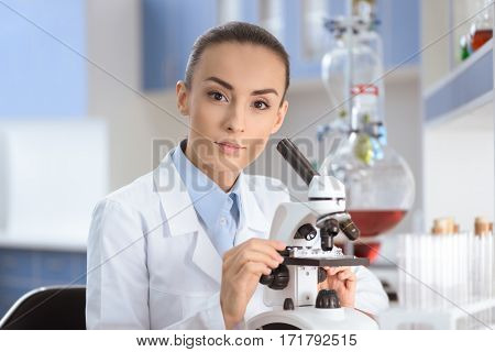 Young woman scientist in lab coat working with microscope and looking at camera