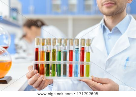 Close-up partial view of scientist holding test tubes with reagents in lab