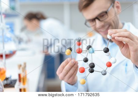 Smiling man scientist in eyeglasses holding molecular model in lab