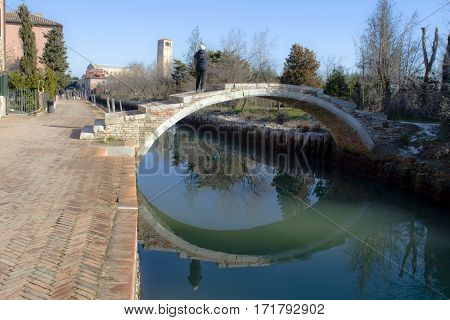 Tourists photographing the landscape from above the Devil's Bridge in Torcello