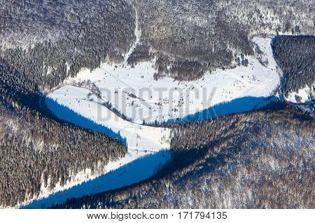 Winter background with a snow-covered dell in wooded hills, trace by snowmobile around the little hunter houses. Captured from above with a drone.