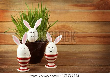 Decorated Easter eggs and pot on wooden background