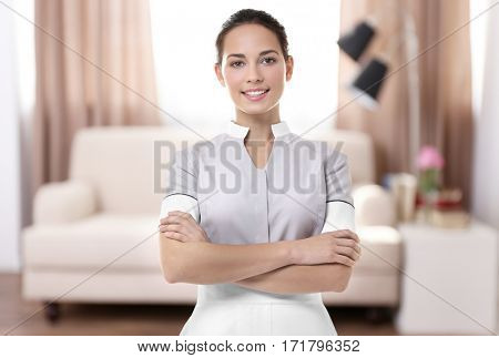 Chambermaid standing on living room background