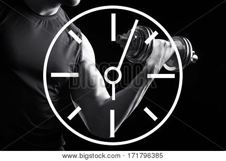 Time concept. Man training with dumbbell on black background