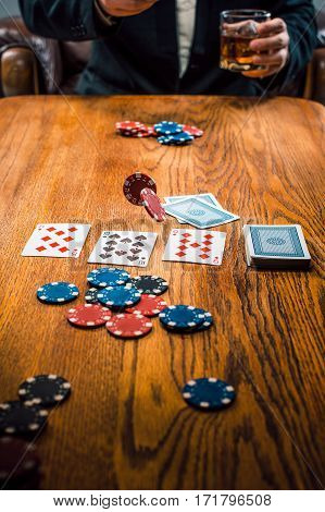 The chips for gamblings, drink and playing cards on wooden table. Poker concept