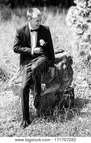 Handsome smiling groom in black suit posing outdoors b&w