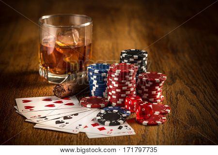 Cigar, chips for gamblings, drink and playing cards on wooden table. Poker concept