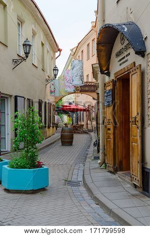 VILNIUS LITHUANIA - JULY 10 2015: Unknown people go near restaurant Naked Bite of Contemporary Cuisine on Stikliu Street in Old Town Vilnius Lithuania