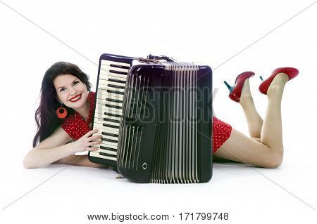 pretty woman in red dress lies with accordion on floor of studio with white background