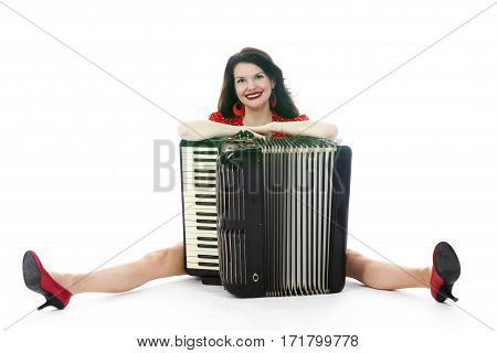 pretty woman in red sits with accordion on floor of studio with white background and smiles