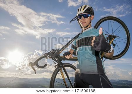 man in helmet and glasses stay on the bicycle under sky with clouds.