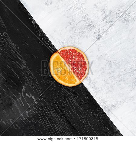 Grapefruit and orange citrus fruit halves on wooden background.