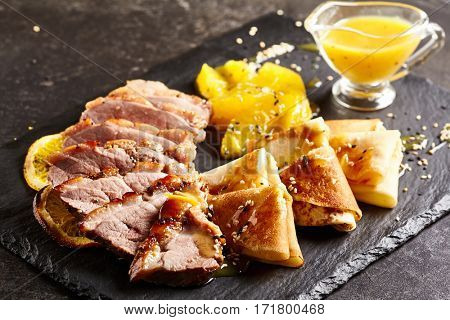 Chinese Cuisine Food - Peking Duck (Beijing Roast Duck) with Orange Sauce on Black Slate Dish. Restaurant Food on Black Slate Background