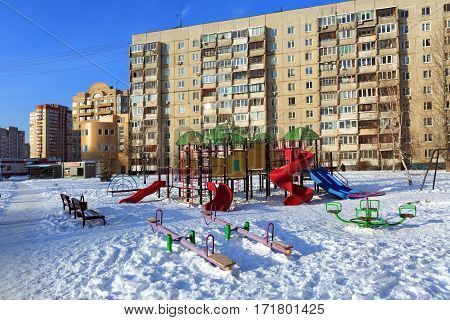 BALASHIKHA/ RUSSIA - JANUARY 21. A children's playground on the background of a multi-storey panel residential building on January 21, 2016. Balashikha, Moscow region, Russia.