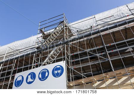 scaffolding with stairs under blue sky on new housing facility in the netherlands and arning signs