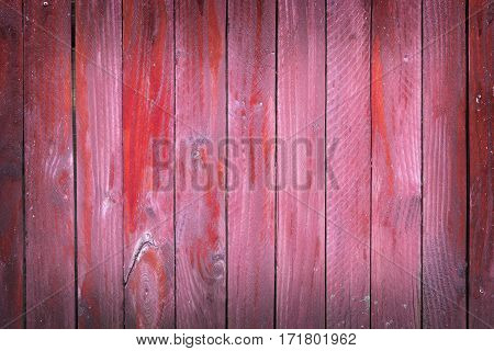 vertical planks of faded red painted worn planks on horizontal piece of fence or door