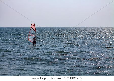 Red windsurf in the sea with ships at horizon in India