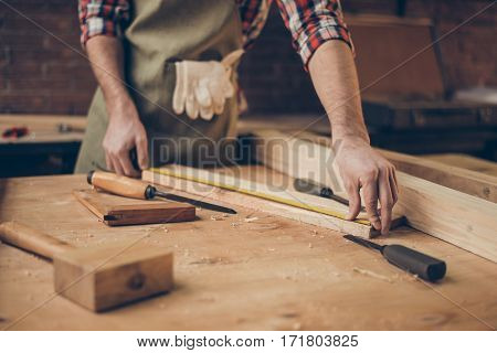Closeup Photo Of  Cabinetmaker's Tabletop.  Craftsman Holding Ruler  On Wooden Planknear Other Tools